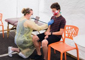 Nurse practitioner Bryana Hinck checks a patient in Thrive Pediatrics' sick-child tent