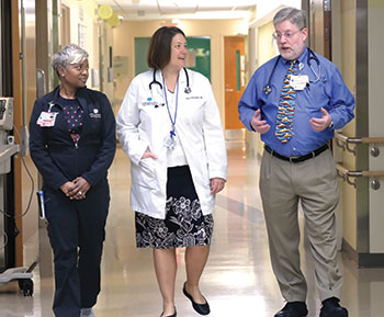 Registered nurse Ebony Cunningham (left) listens as Drs. Sara Horstmann (center) and Joe Sechler (right) discuss their new Pediatric Hospital Medicine certification. Photo by Nancy Pierce.